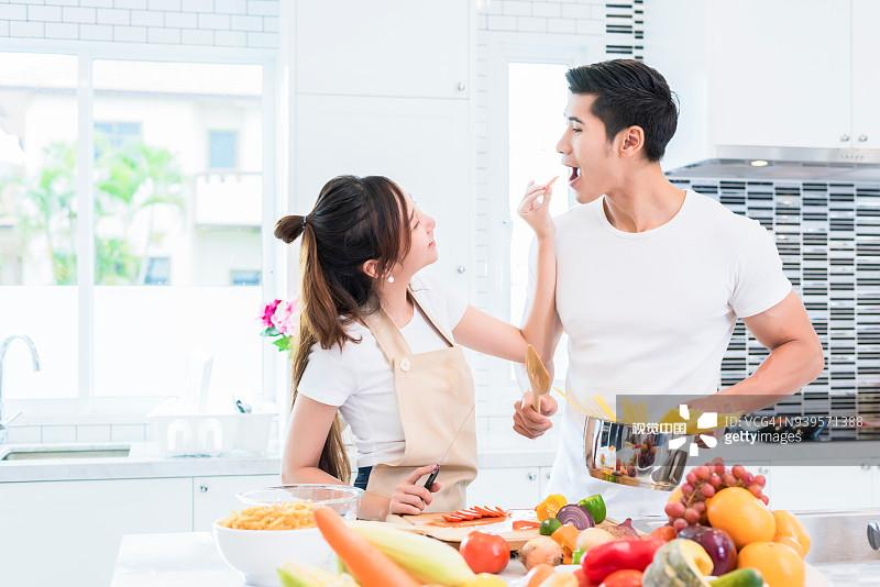 Young Couple Cooking Food While Standing In Kitchen图片素材_创意图片 - 视觉中国